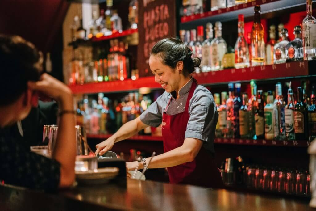 Bartender with apron making drinks behind a bar